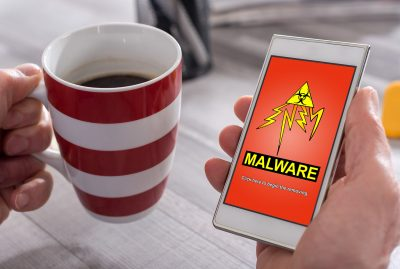 "Picture of a man's hand holding a phone with ""Malware"" written across the screen, Malware on a Smartphone or Tablet"